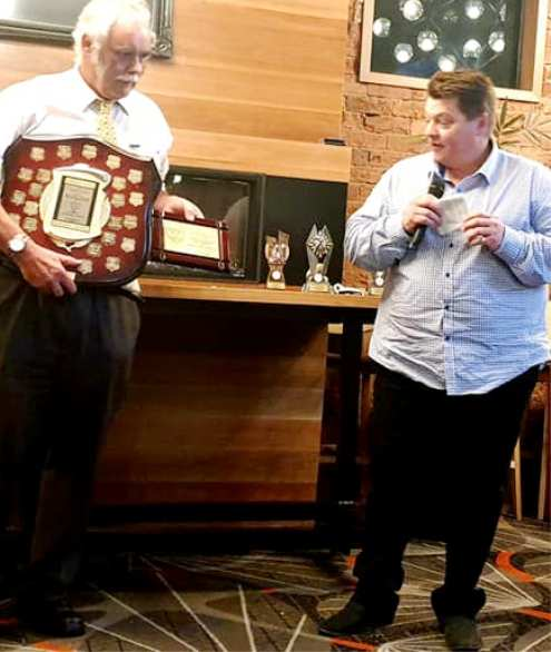 Mark Gauci responds to the announcement of his Lindsay Jones Award, while President Charlie Walker holds his plaque and the perpetual trophy.
